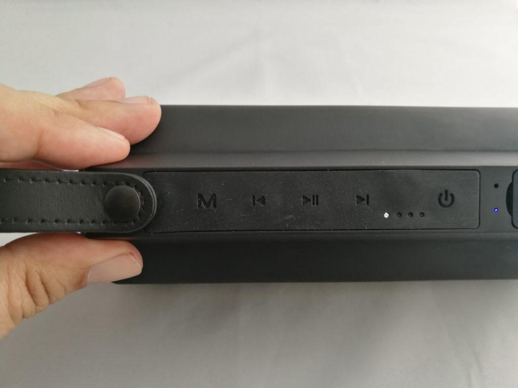 Les boutons permettent de naviguer entre les morceaux. Notez les LED qui indiquent la charge et la source, ainsi que la dragonne de transport.